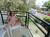 Mature posing naked on the balcony