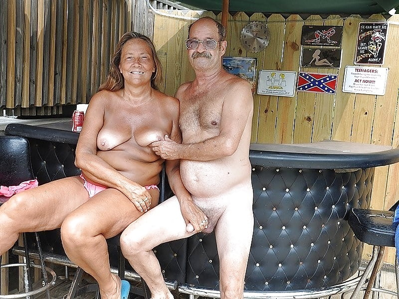 Older couple jumping naked into pond