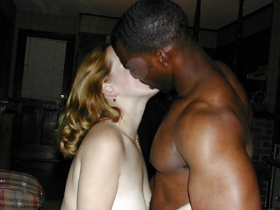 Pregnant white girl with black partner holding tummy and kissing stock photo