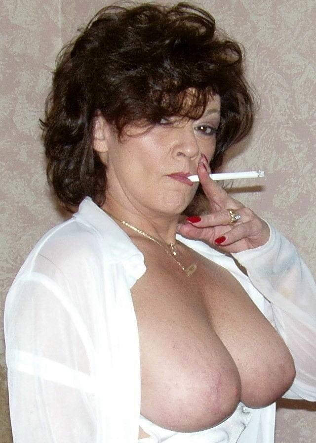 Portrait of beautiful rebellious brunette woman smoking cigarette